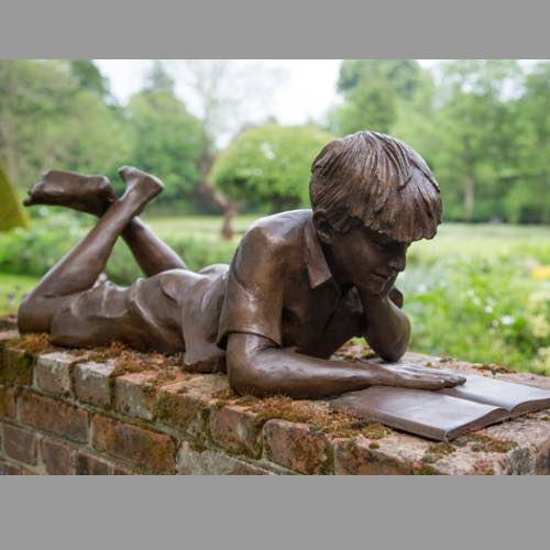 Reading boy a garden sculpture by Kate Denton